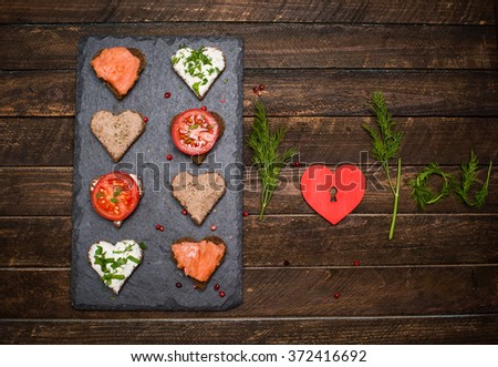 Mini canapes heart shape with different toppings on black slate board, red heart and I love you made of herbs on rustic wooden background. Delicious appetizers. Valentines day food. - stock photo