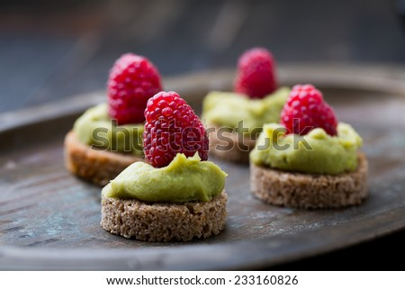 mini canapes with guacamole and raspberries - stock photo