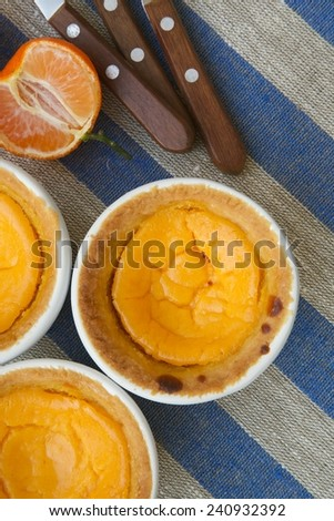 Mini cheese cakes with tangerines in white ceramic moulds. Pieces of tangerines and dessert spoons on a sackcloth - stock photo