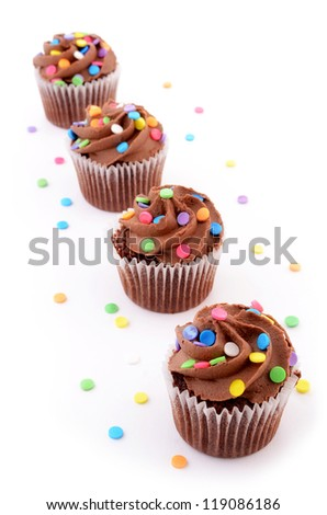 Mini chocolate cupcakes with colorful sprinkles on white background - stock photo