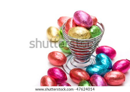 Mini chocolate eggs in wire eggcup - stock photo