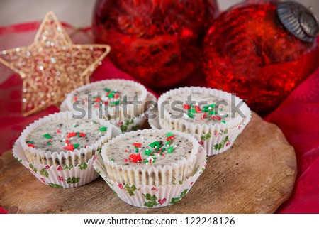 Mini cookies and cream cheesecakes in muffin forms with red Christmas tree balls - stock photo