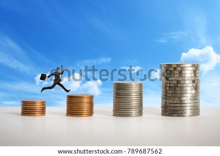 Mini doll and Stacks of coins in a growth financial concept.