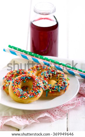Mini donuts with sweet sprinkles on plate