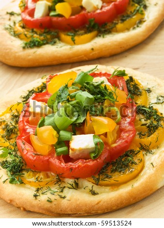 Mini focaccia with tomatoes, feta cheese and herbs. Shallow dof. - stock photo