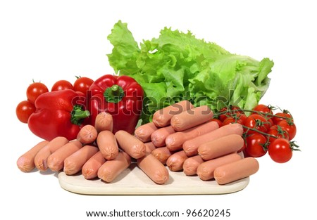 mini frankfurters with paprika, tomatoes and green salad are waiting for homemakers hand - stock photo