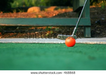 Mini-golf ball and putter - stock photo