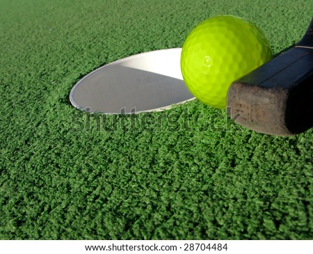 Mini golf club ready to sink the putt with a yellow ball in a hole on artificial green turf at a miniature golfing amusement park - stock photo