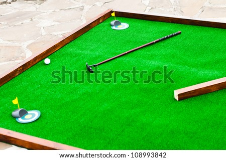 Mini golf field with ball and golf club - stock photo