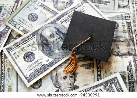 mini graduation cap on top of a pile of cash