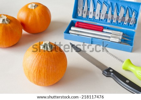 Mini Halloween pumpkins with carving tools - stock photo