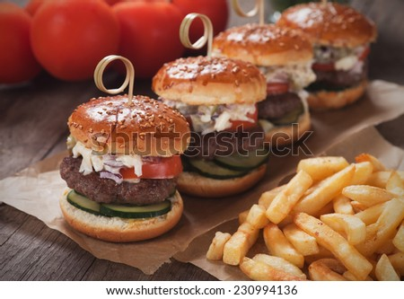 Mini hamburgers with french fries served as appetizer on wooden table - stock photo