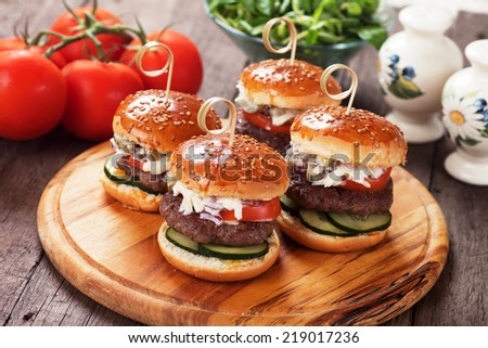 Mini hamburgers with tomato and cucumber on wooden board - stock photo