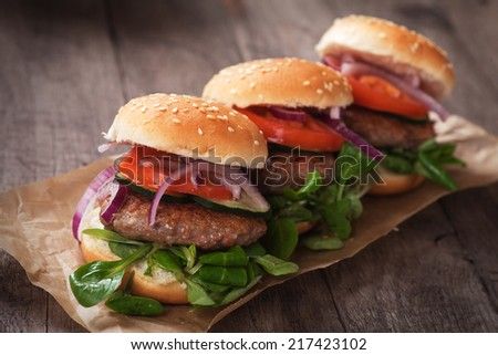 Mini hamburgers with tomato and onion on wooden table - stock photo