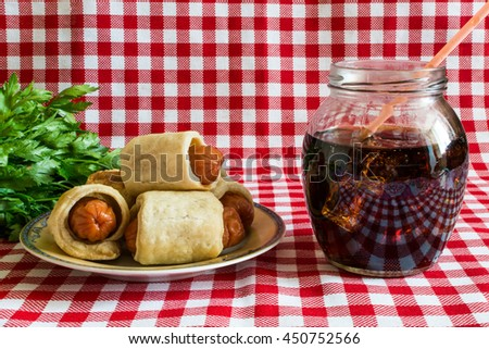 Mini hot dog homemade - (sausage in pastry) with herbs and cola on a plaid background. In Europe, the sausage in pastry served with different sauces, eat them with a fork. - stock photo