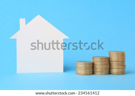 Mini house with money on blue - stock photo