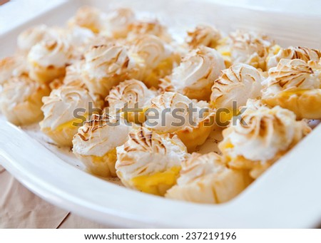 Mini Lemon Meringue Tarts in porcelain tray - stock photo
