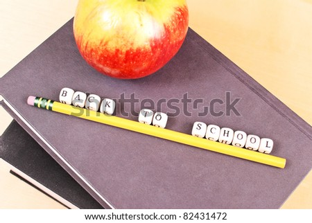 Mini Letters Spelling Out Back To School on Books - stock photo