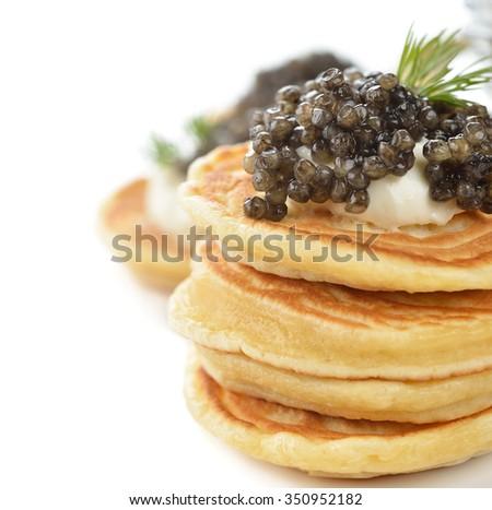Mini pancakes with black caviar on a white background - stock photo