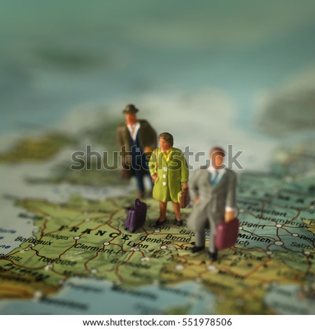 Mini people with luggage on a map, on France in Europe.