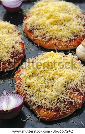 Mini pizzas or small pellets covered with cheese close-up - stock photo
