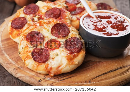 Mini pizzas with salami, cheese and tomato - stock photo