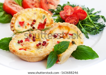 Mini quiche filled with vegetables with salad.Focus on the front pie. - stock photo