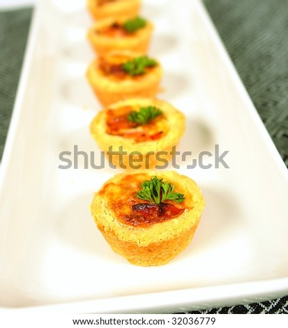 Mini quiche or pies with ham bacon salami and cheese - stock photo