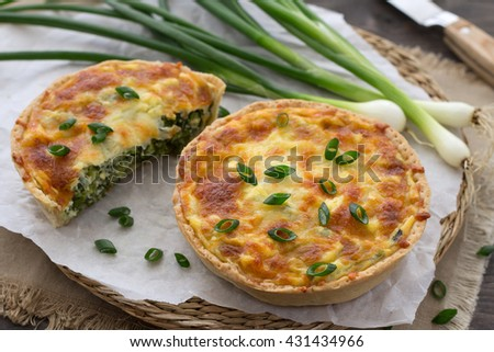 Mini quiche with green onions and cheese on a wooden background - stock photo