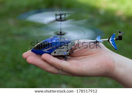 Mini RC helicopter rises over hand - stock photo