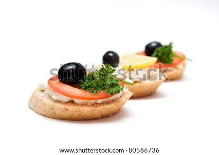 Mini sandwiches - bread with cream cheese, tomato, lemon, olives and parsley - stock photo