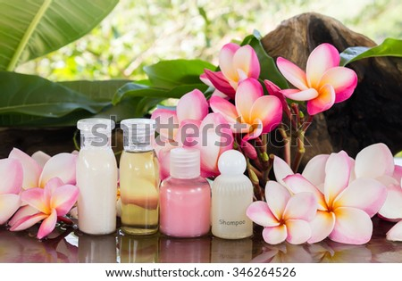 Mini set of bubble bath and shower gel liquid on wood shelf decorated with pink flower plumeria on green nature relaxing feeling background - stock photo