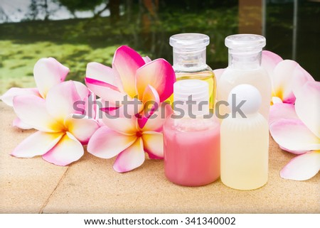 Mini set of bubble bath and shower gel on rock tile floor beside the pool decorated with fragrant beautiful flower  - stock photo