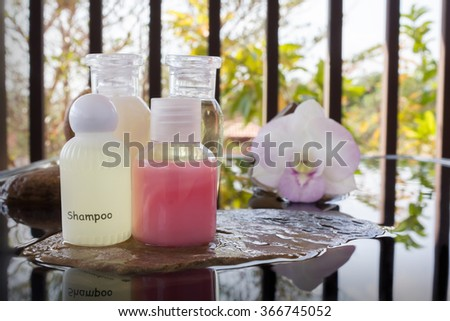 Mini set of bubble bath and shower liquid gel with orchid flowers on pebble and water - stock photo