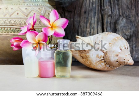 Mini set of bubble bath shower gel liquid with pink flower and sea conch shell in relax mood - stock photo