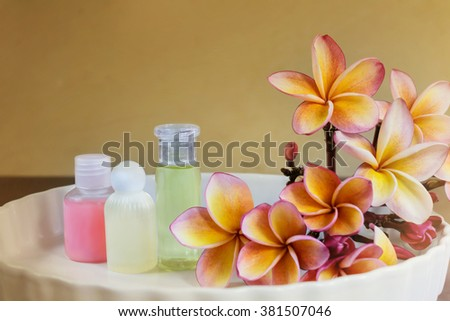 Mini set of shampoo or shower bath on white plate with flowers bunch in vintage colour tone - stock photo