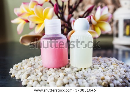 Mini set of shower bath soap, shampoo,conditioner on pebble and flower background - stock photo