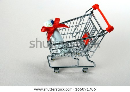 Mini shopping cart with hundred euro and red ribbon, top view - stock photo