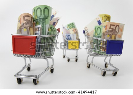 Mini shopping carts with euro banknotes on white background - stock photo