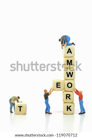 Mini workmen building together in teamwork concept with copy space - stock photo