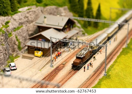 miniature alpine railroad model with overhead electric power lines - stock photo