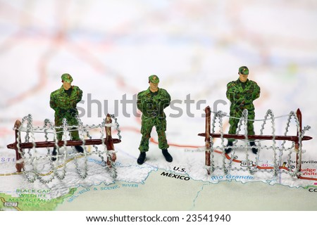 Miniature border patrol guards stand on a map at the USA/Mexico border with barbed wire. Border protection concept. - stock photo