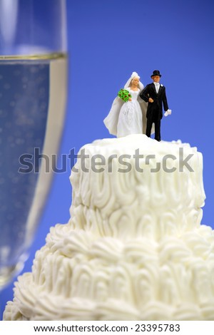 Miniature bride and groom on top of a wedding cake. There is a glass of champagne in the background. Marriage concept. - stock photo