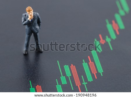 miniature business man standing on the candlestick stock chart - stock photo
