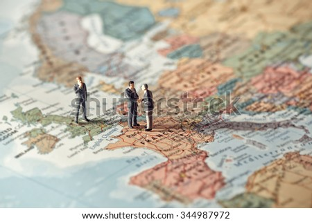 Miniature business people on map of Europe. Color tone tuned. - stock photo