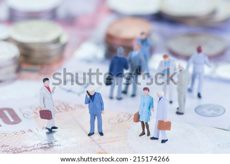 Miniature business people on pound sterling banknotes - stock photo