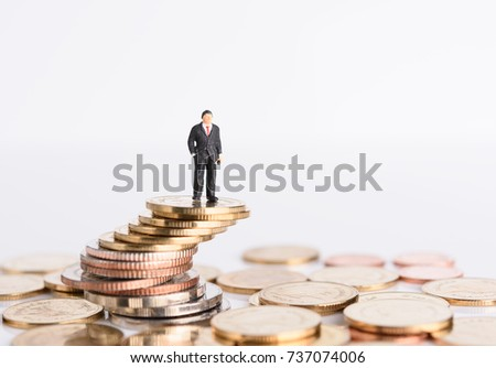Miniature business people stand on money coins isolated on white,Business successful concept
