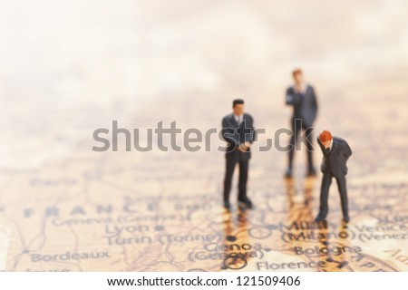 miniature businessman figurines on world map background - stock photo