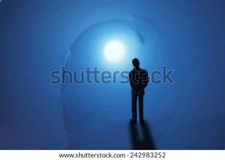 miniature businessman stand front of tunnel and light  - stock photo