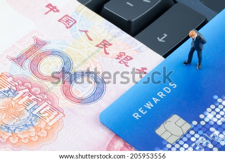 miniature businessman standing on the computer keyboard with Chinese banknote and credit card - stock photo